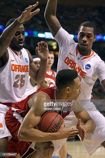The smothering defense of Syracuse's Rakeem Christmas left and Kris Joseph right forces Wisconsin's Ryan Evans center to call a timeout so the...
