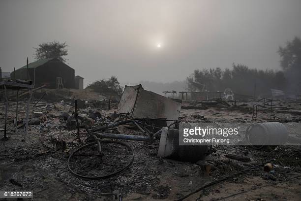 The smouldering remains of shacks and makeshift shops in the notorious Jungle camp after migrants set fire to them last night on October 26 2016 in...