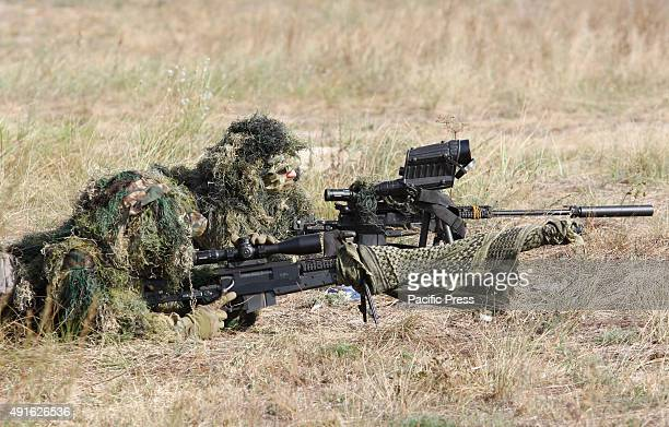 The snipers of the Ukrainian National Guard takes up a position during a training session on the shooting rangesome 80 km from Kiev Ukraine Russian...