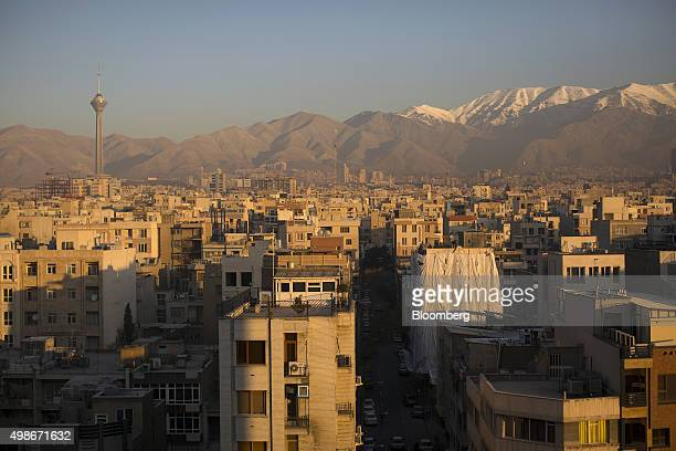 The snow capped peaks of the Alborz mountain range stand beyond buildings and rooftops on the city skyline in Tehran Iran on Wednesday Nov 25 2015...