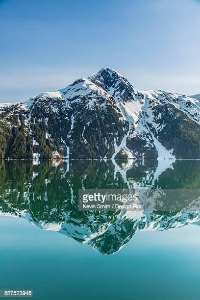 the snow covered chugach mountains reflected in the waters of barry arm in springtime, chugach national forest - chugach mountains stock pictures, royalty-free photos & images