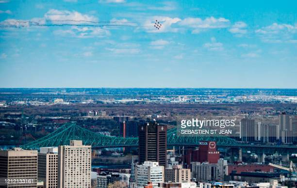 "The Snowbirds, the Royal Canadian Air Force air acrobatics team, fly over Montreal in a morale-building tour of Canada called ""Operation..."