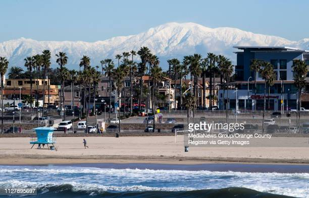 The snowcapped mountains are seen from the Huntington Beach pier in Huntington Beach CA on Wednesday February 6 2019