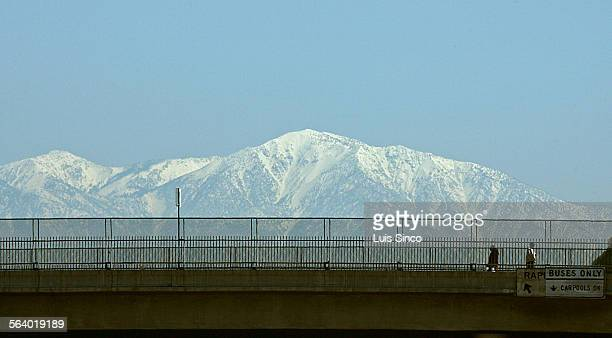The snow–capped peak of Mount Baldy looms in the distance as pedestrians cross a bridge over Interstate 10 in City Terrace Photo taken 3/22/06