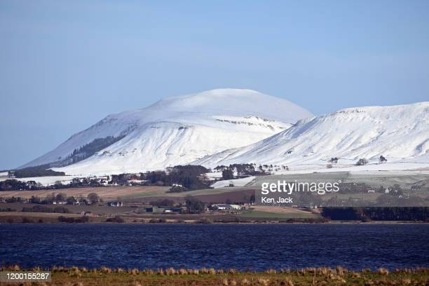 The snowclad slopes of the Lomond Hills rise above Loch Leven, on February 11, 2020 in Kinross, Scotland .