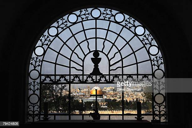 The snow-covered golden Dome of the Rock Islamic shrine in the Old City is seen behind the glass-and-lead window of Dominus Flavit, a Catholic chapel...