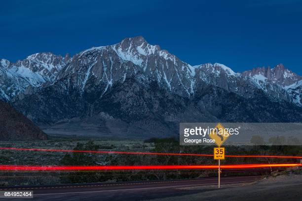 The snowcovered Sierra Nevada Mountains are viewed from the scenic Alabama Hills as a car on Whitney Portal Road streaks across the picture before...