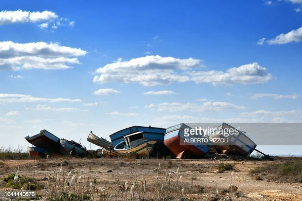 TOPSHOT The socalled boat cemetery where skiffs are dumped after the migrants and refugees' crossing from North Africa is pictured in Lampedusa on...