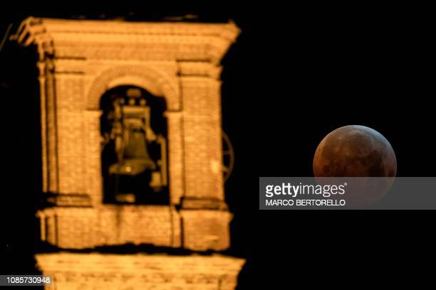 The socalled Super Blood Wolf Moon is pictured into Earth's dark umbral shadow during a total lunar eclipse over the San Bernardino's Church in...