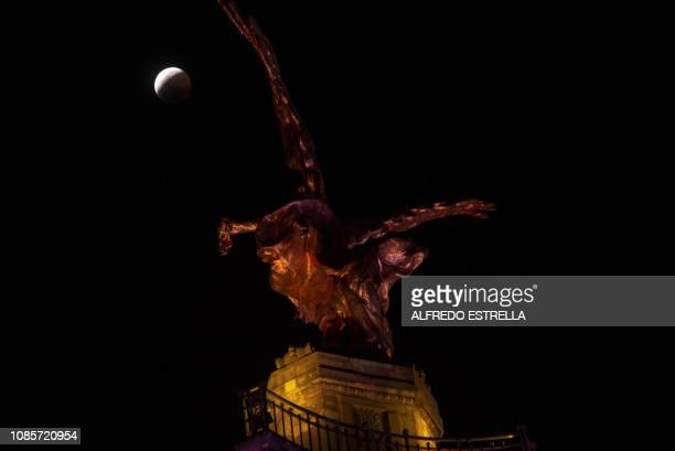 The socalled Super Blood Wolf Moon slips into Earth's dark umbral shadow during a total lunar eclipse over Angel de la Independencia in Mexico City...