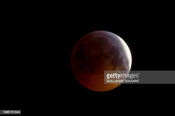 The socalled Super Blood Wolf Moon slips into Earth's dark umbral shadow during a total lunar eclipse above the Tours's cathedral on January 21...