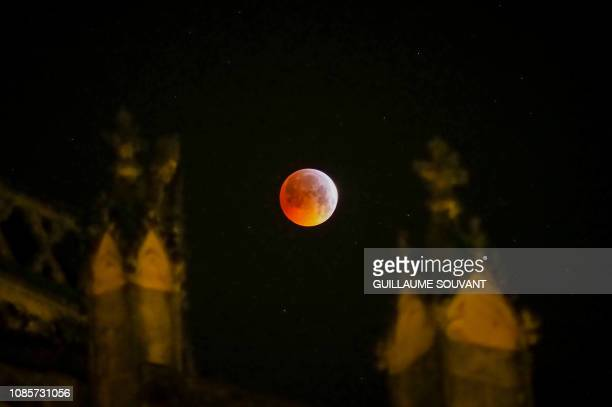 The socalled Super Blood Wolf Moon slips into Earth's dark umbral shadow during a total lunar eclipse behind the Tours's cathedral on January 21...