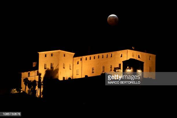 The socalled Super Blood Wolf Moon starts exits Earth's dark umbral shadow during a total lunar eclipse over the Castello della Manta in Manta near...
