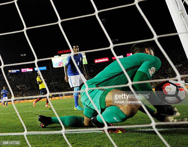 The soccer ball bounces off the shoulder of goalkeeper Alisson Becker of Brazil and bounces into the goal during the second half against Ecuador but...
