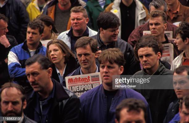 The Socialist Militant newspaper is held by a man alongside other workers listen to speeches in central Liverpool during the bin men strike of 1991...
