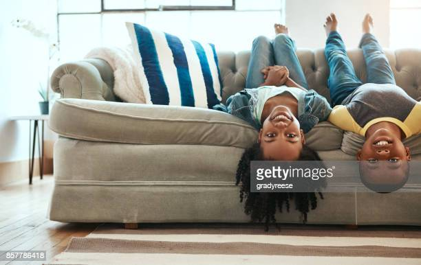 the sofa is a magical vehicle that transports us anywhere - african american family home stock photos and pictures