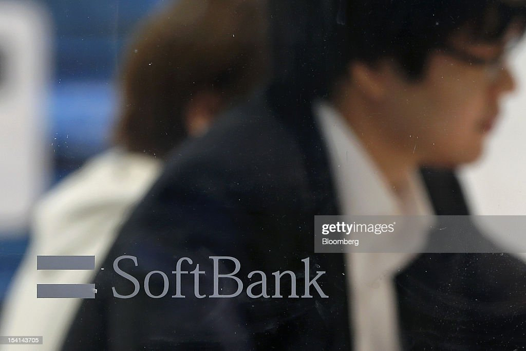 The Softbank Corp. logo is seen on a window at the company's store as customers sit at a counter in Tokyo, Japan, on Monday, Oct. 15, 2012. Softbank agreed to pay $20.1 billion to acquire about a 70 percent stake in Sprint Nextel Corp. as Japan's third-biggest mobile-phone operator seeks growth overseas amid a declining local market. Photographer: Kiyoshi Ota/Bloomberg via Getty Images