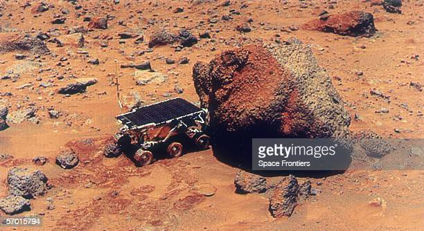The Sojourner Rover uses its Alpha Proton XRay Spectrometer to analyse the Yogi Rock on the surface of Mars during the Mars Pathfinder exploratory...