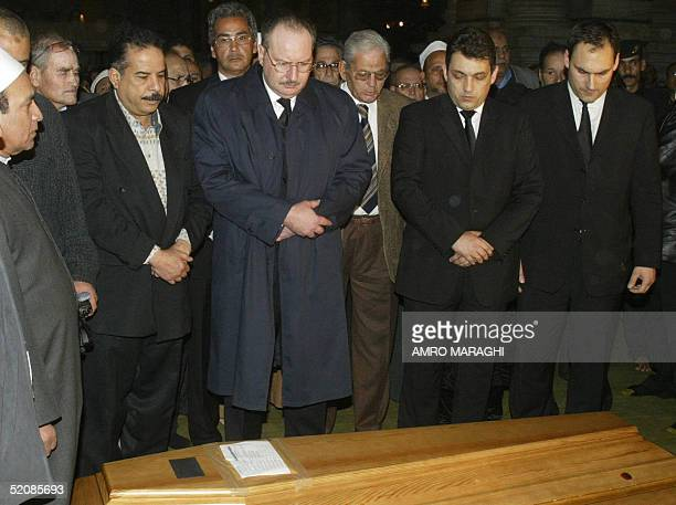 The son of Egypt's late King Faruq Ahmed Fuad prays along with unidentified mourners over the coffin of his sister Fawzia during her funeral at the...