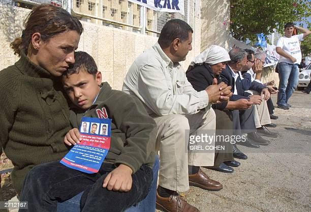The son of Israeli Druze soldier Omar Suad is comforted by his mother as he holds a leaflet with the pictures of three Israeli soldiers, including...