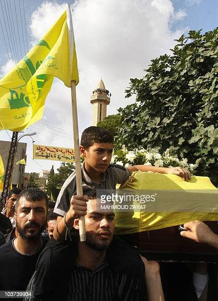 The son of killed Shiite Muslim Hezbollah member Ali Jawad carries the Hezbollah flag during the funeral procession of his father in the southern...