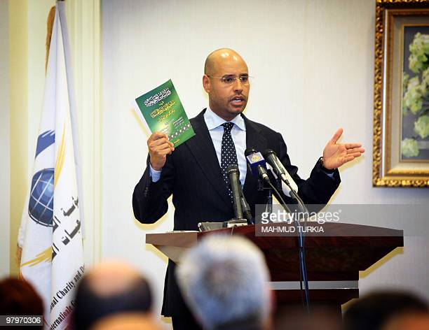 The son of Libyan leader Moamer Kadhafi Seif alIslam holds a book written by freed Islamists during a press conference he held in Tripoli on March 23...