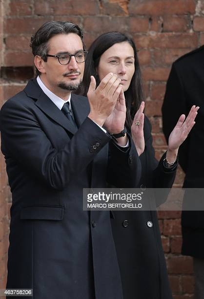 The son of Michele Ferrero Giovanni Ferrero flanked by his wife Paola applaud the coffin of his father during the funeral on February 18 2015 in Alba...