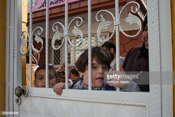 The son of the headmistress pokes his head through the gated fence at The 'School for the Sons and Daughters of the Martyrs of Syria' was opened by a...