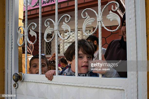 The son of the headmistress poks his head through the gated fence at The Syrian School for the Son's and Daughters of the Martyer's on October 312013...