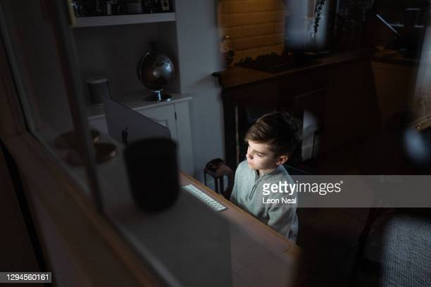 The son of the photographer begins the new school term of 2021 at home by watching an online introduction from his teacher, on January 05, 2021 in...