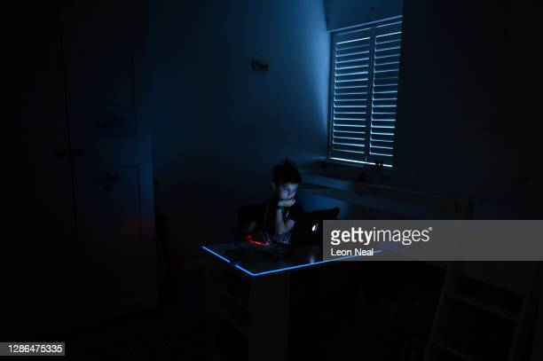 The son of the photographer is seen as he plays an online computer game in his bedroom on November 13, 2020 in London, England. As the second...