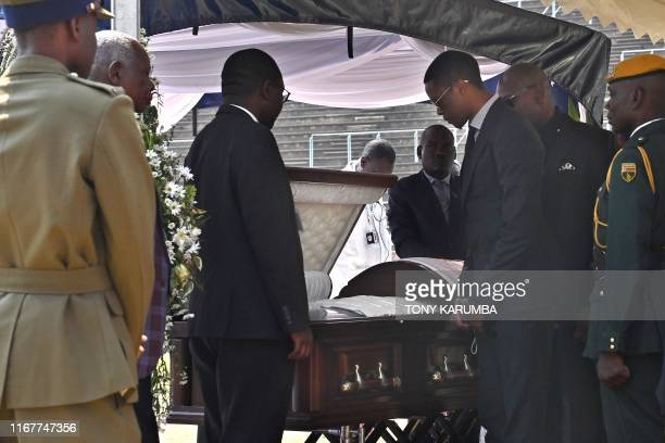 TOPSHOT The son of Zimbabwe's former President the late Robert Mugabe Robert Junior looks into the casket bearing his father's remains during a...