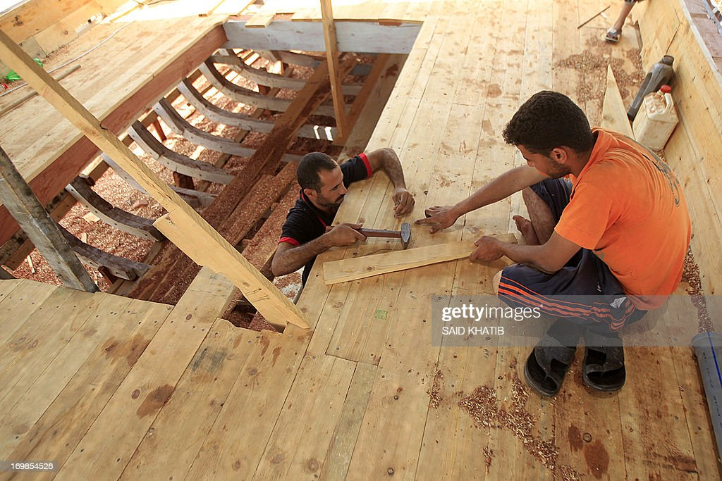The sons of Abdullah al-Najjar, 55-years-old, construct a new fishing boat in front of his house on the seaside in the Rafah town in the southern Gaza Strip near the border with Egypt on June 3, 2013