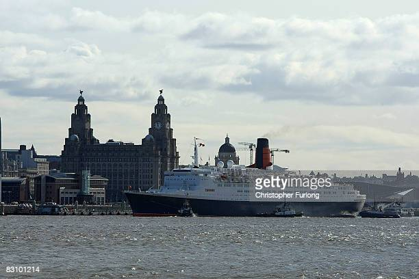 The soon to be decommissioned Queen Elizabeth II liner docks in front of the Liver building on the River Mersey during her final farewell voyage on...