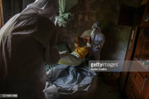 The SOS Funeral team members wearing personal protective equipment carry the body of Lucia Rodrigues dos Santos, 60 years old, whose death is not...
