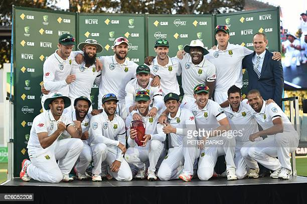 The South Africa cricket team poses for photos with the trophy after beating Australia in the series at the end of the game on the fourth day of the...