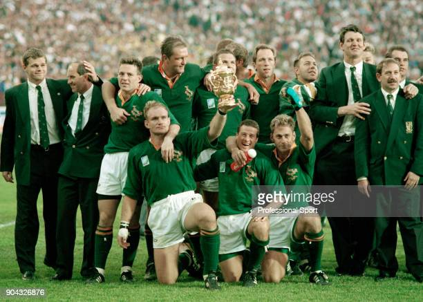 The South Africa team celebrate with their captain Francois Pienaar holding the trophy after their victory in the Rugby Union World Cup Final against...