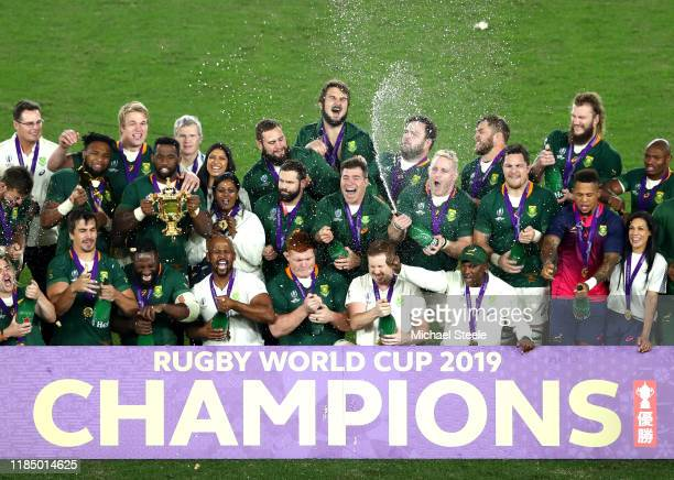 The South Africa team celebrates as Siya Kolisi of South Africa holds the Web Ellis cup following their team's victory against England in the Rugby...
