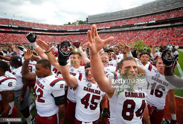 The South Carolina Gamecocks celebrate their 20-17 win over the Georgia Bulldogs in the second overtime at Sanford Stadium on October 12, 2019 in...