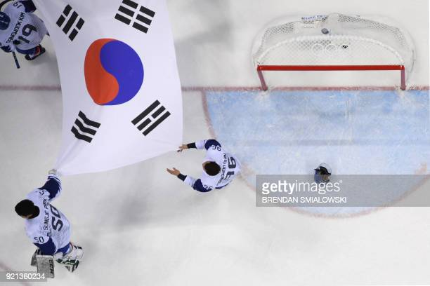 The South Korea flag is carried across the ice after the men's playoffs qualifications ice hockey match between Finland and South Korea during the...