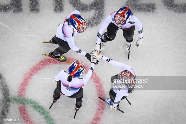 The South Korea team hold hands before winning the women's 3,000m relay short track speed skating heat event during the Pyeongchang 2018 Winter...
