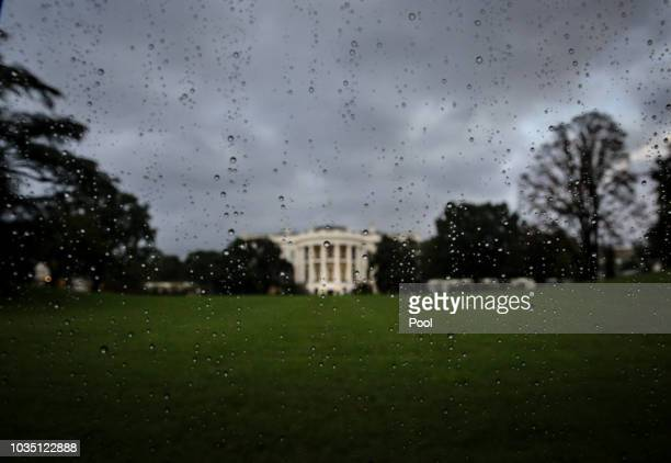 The South Lawn of the White House is seen from a car window covered with rain drops as the President Donald Trump's motorcade heads to the Trump...