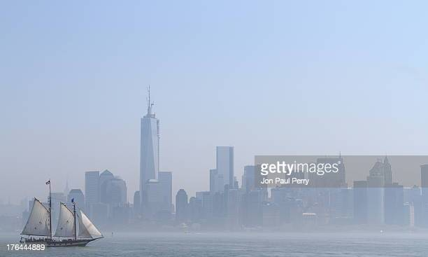 CONTENT] The southern tip of Manhattan seen from the Hudson River through an early morning blue mist with a tall mast sailing ship and One World...