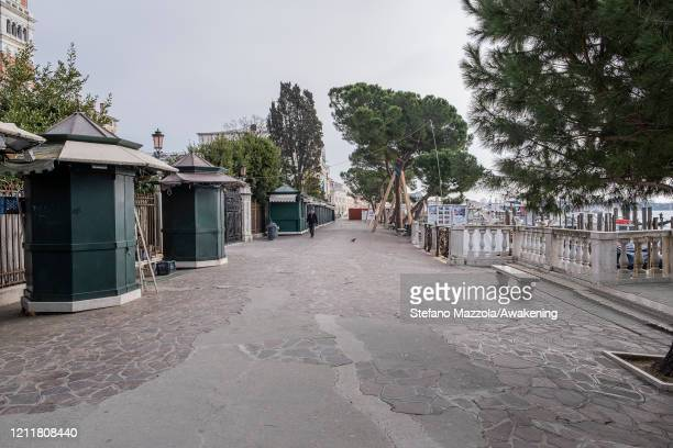 The souvenir shops are closed near Piazza San Marco on March 11 2020 A local walks near the Grand Canal with a protective face mask in Venice Italy...