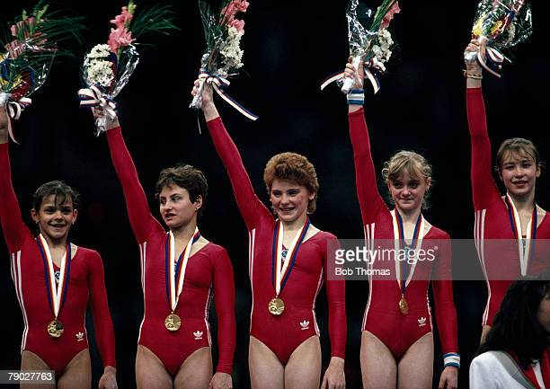 The Soviet Union women's gymnastics team celebrate together on the podium after winning the gold medal in the Women's team allaround gymnastics event...