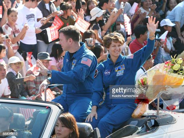 The Space Shuttle Discovery crew commander Eileen Collins and pilot Jim Kelly wave to people as they parade in Discovery crew member Soichi Noguchi's...