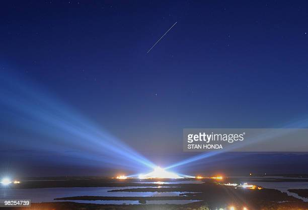 The space shuttle Discovery streaks across the sky following lift-off from the Kennedy Space Center in Florida on April 5, 2010. Discovery carries a...