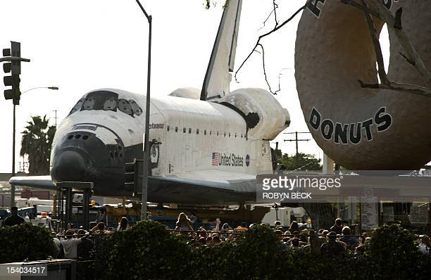 The Space Shuttle Endeavour stops in front of the iconic Randy's Donuts shop as it travels through the streets of Los Angeles on its final journey to...