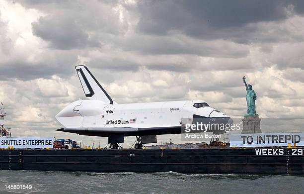 The space shuttle Enterprise is brought past the Statue of Liberty on a barge on June 6 2012 in New York City The shuttle is on it's way to the USS...
