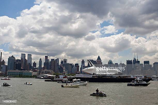 The space shuttle Enterprise is pulled past the New York skyline on a barge on June 6 2012 in New York City The shuttle is on it's way to the USS...